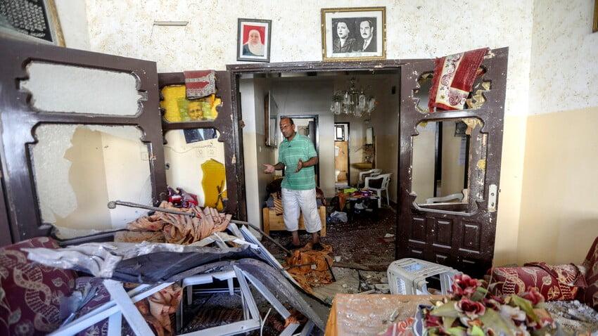 En man i ett hem förstört i en flygräd i Gaza.