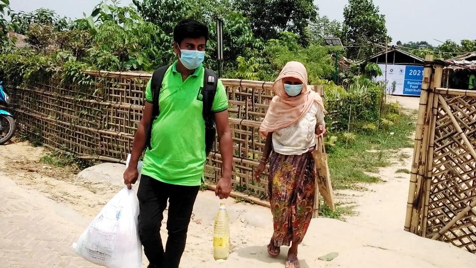 Två personer i Cox Bazar bär på mat från Islamic Relief