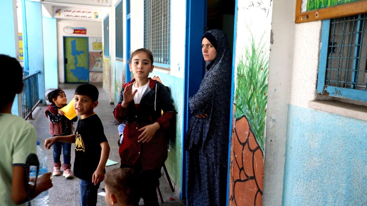 En familj som tvingats fly sitt hem i Gaza och har sökt skydd i en skola.