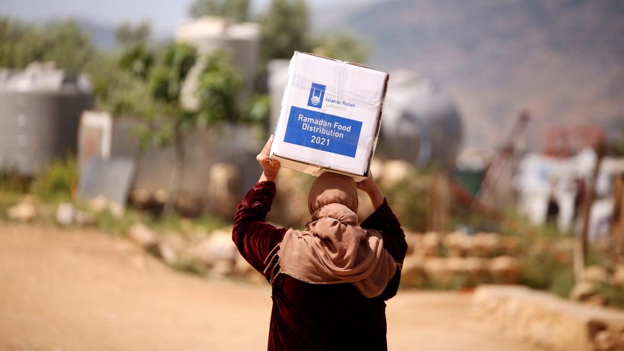 En kvinna bär på en kartong med mat i Libanon