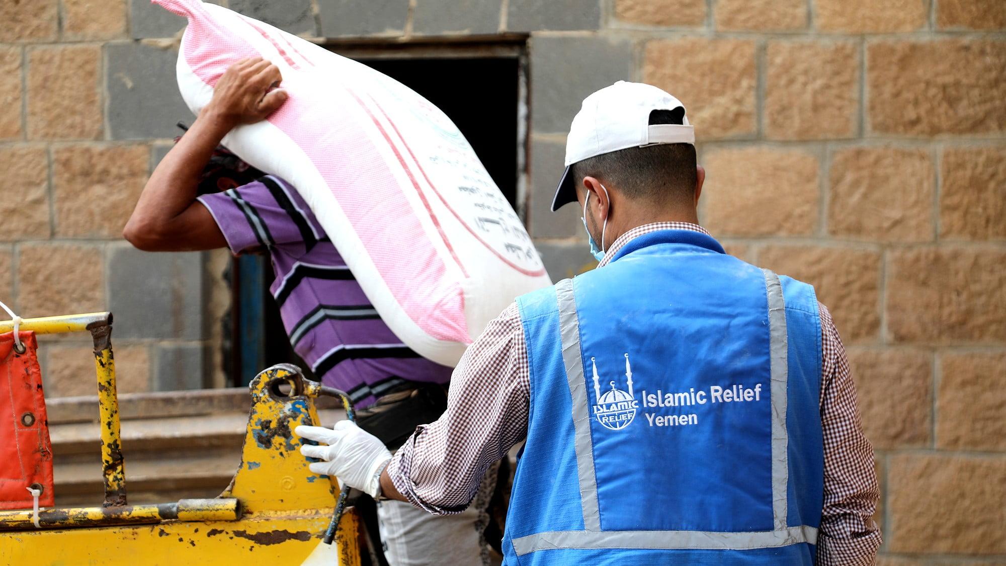Två personer med en säck med mat i Jemen