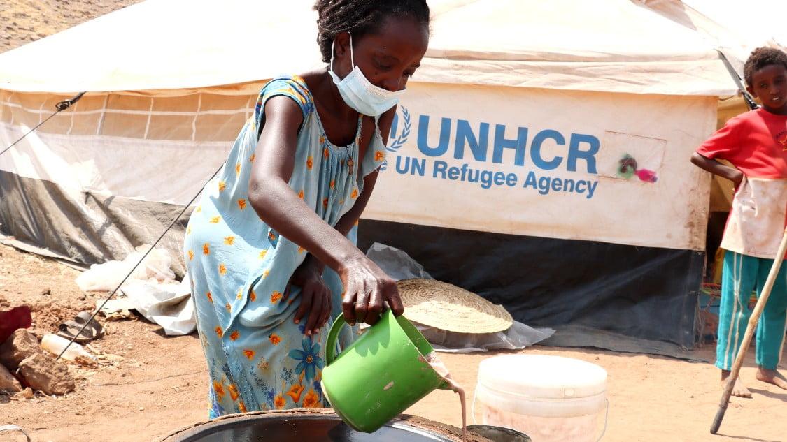 Mulu bakar injera-bröd i flyktinglägret i Sudan