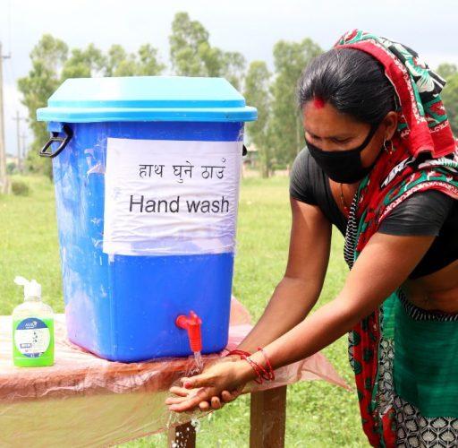 Kvinna tvättar händerna vid en handtvättsstation i Nepal
